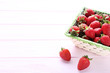 Fresh strawberries in basket on pink wooden table