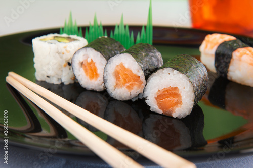 mixed sushi on black plate with orange glass and Japanese chopsticks