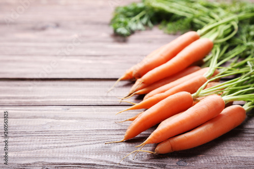 Leinwanddruck Bild Fresh and sweet carrot on wooden background