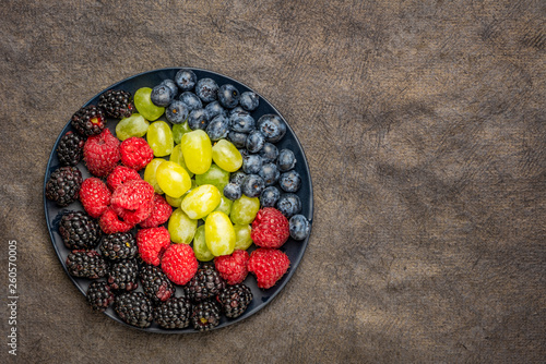 berries and grapes on a black plate - 260570005