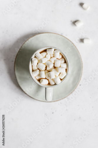 Hot chocolate with marshmallow in a ceramic mug over textured white background. Minimalist style, top view, copy space.