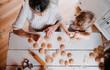 Leinwandbild Motiv A top view of senior grandmother with small toddler boy making cakes at home.