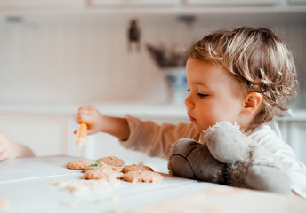 A small toddler girl sitting at the table, decorating cakes at home.