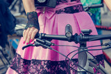 Concept: women on bicycles. Hands holding the handlebars. Pink skirt with black lace