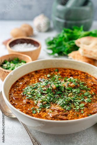 Traditional Georgian soup Kharcho in bowl on gray concrete background. Selective focus. - 260584877