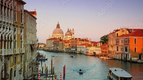 Venice, Italy:Grand Canal with large and small boats along with famous gondolas, along sea-lined paths with palaces and facades, in the background Santa Maria della Salute
