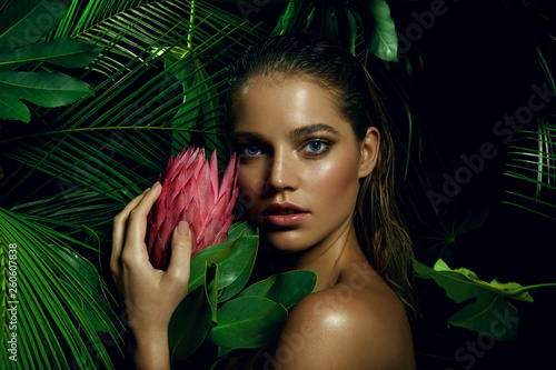 canvas print picture A beautiful tanned girl with natural make-up and wet hair stands in the jungle among exotic plants.