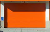 Orange door, garage and sidewalk