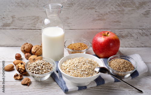 canvas print picture Breakfast with oats, flax seeds, sunflower seeds, sesame seeds, milk, apple, walnuts, almonds and hazelnuts on a white wood background.