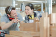artisan teaching female apprentice woodworking in carpentry shop - 260659892