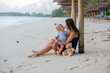 Leinwanddruck Bild - Happy beautiful fashion family, mom and baby, hugging, casually dressed, enjoying the sunrise on the beach in Mauritius