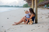 Happy beautiful fashion family, mom and baby, hugging, casually dressed, enjoying the sunrise on the beach in Mauritius