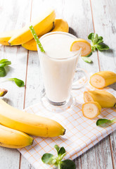 Fresh milk, banana on wooden table, assorted protein cocktail with fresh fruits. Natural background.