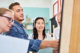 Maler und Besucher zusammen vor einer Staffelei