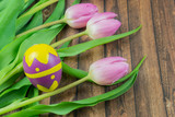 Fototapeta Tulipany - Fresh tulips with a beautiful Easter egg, wooden table and copy space © Angela Rohde