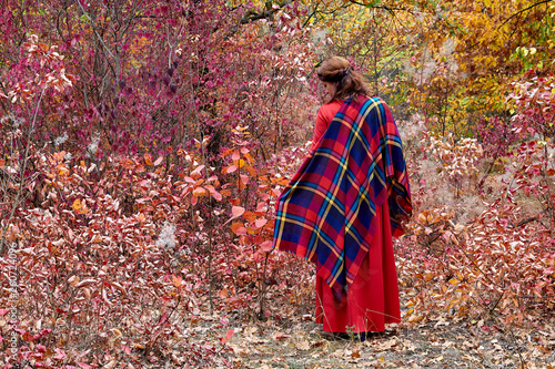 fototapeta na ścianę Middle-aged brunette woman in a red dress with checkered shawl posing in bright, fairy autumn forest. Back view