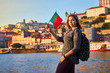 Quadro Young woman tourist with portuguese flag enjoying beautiful landscape view on the old town (Ribeira historical quarter) and river Duoro during the sunset in Porto city, Portugal