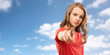 Leinwanddruck Bild - accusing gesture and people concept - teenage girl with long hair in red t-shirt pointing finger to you over blue sky and clouds background