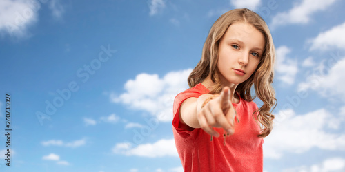 Leinwanddruck Bild accusing gesture and people concept - teenage girl with long hair in red t-shirt pointing finger to you over blue sky and clouds background