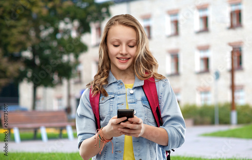 Leinwandbild Motiv education, school and people concept - happy smiling teenage student girl with bag and smartphone over campus background