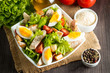 Fresh salad made of tomato, ruccola, chicken breast, eggs, arugula, crackers and spices. Caesar salad in a white, transparent bowl on wooden background - 260740452