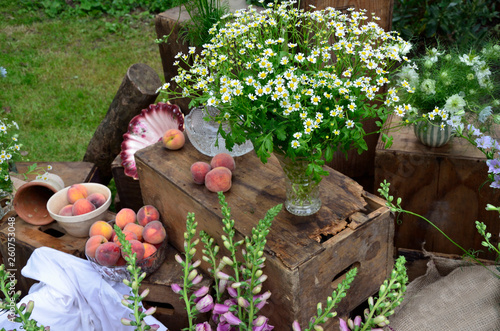 A garden still life arrangment of flowers, fruit and other assorted items of interest © Garden Guru