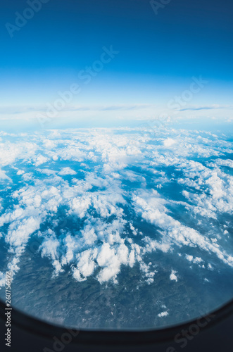 View of the sky above clouds over the earth through the airplane window, flying high. Deep blue sky with white clouds. - 260756492