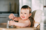 Cute little girl sitting in baby chair and drinking water