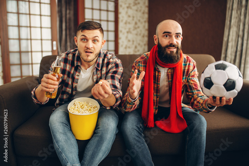 Two football fans wathing tv broadcast at home