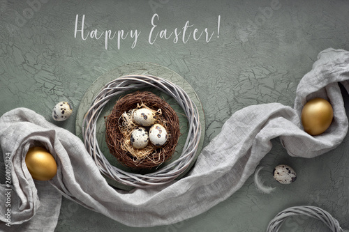 Easter flat lay on dark background with quail eggs in the nest, linen fabrique and two golden eggs on dark - 260805824