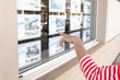 woman hand looks at the window of a real estate agency in the street - 260853067
