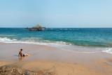 Mężczyzna siedzi w piasku przed morzem oglądając krajobraz. Mazunte Beach, Oaxaca, Meksyk.