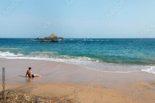 canvas print picture Homme assis dan le sable en face de la mer en train de regarder le paysage. Plage de Mazunte, Oaxaca, Mexique.