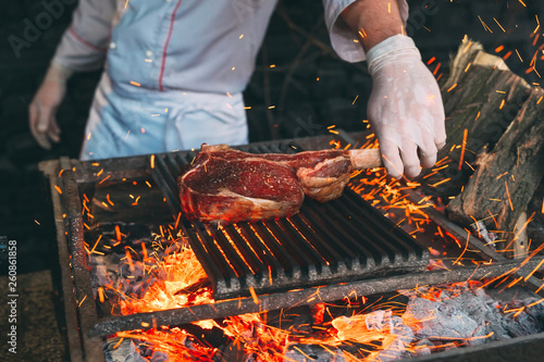 Chef Cooking steak. Cook turns the meat on the fire. - 260861858