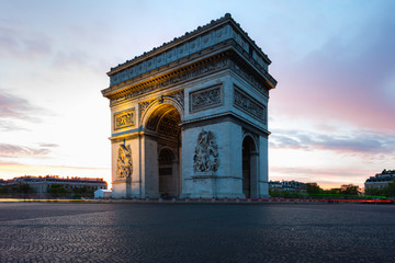 Paris street during sunrise with the Arc de Triomphe in Paris, France.