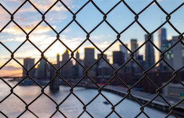 New York City skyline seen through a chainlink fence in Manhattan
