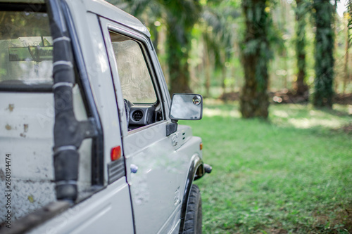 fototapeta na ścianę Close-up background view of the ear, auto glass and exterior body used in the countryside, blurred by sunlight and use, often used in agriculture or in rubber plantations, oil palm