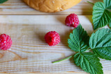 Ripe raspberry branch on wooden background. harvest red berries and green leaves