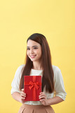 Asian woman is holding a gift box in yellow background