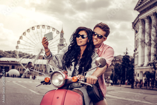 Leinwandbild Motiv Positive nice couple taking photos of themselves