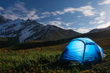 Tourists camp in mountains at night. Hikers tent in night mountain valley