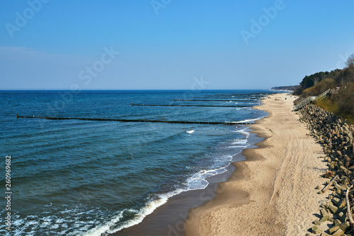 sandy beach and wooden breakwater on the Baltic coast in  Poland. © GKor