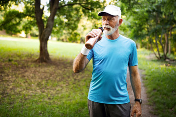 Portrait of athletic mature man after run. Handsome senior man resting after jog at the park