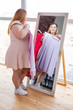 Pleasant good looking woman choosing between dresses