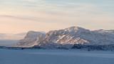 Calm winter landscape during sunrise in light grey sky in Stora Sjöfallets Nationalpark Lappland Sweden, snow covered mountains Hallji, Njavvetjahkka, frozen lake Suorvajaure, view from Vakkotavare