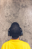 back of asian teenager with headphone listening music on grunge texture cement wall background