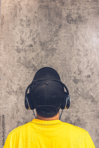 back of asian teenager with headphone listening music on grunge texture cement wall background - 260985414