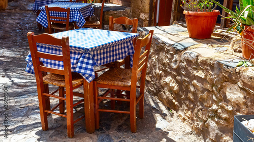 Street view with blue and white cloth tables in greek restaurant tavern in ancient town, Greece