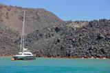 Yacht in front of volcanic coast, Santorini, Greece