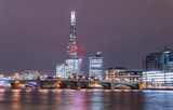 London skyline from the Thames river banks. Bright city lights in the dark sky